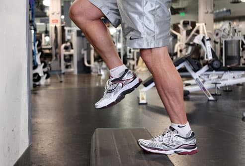 Man doing calf raises on step