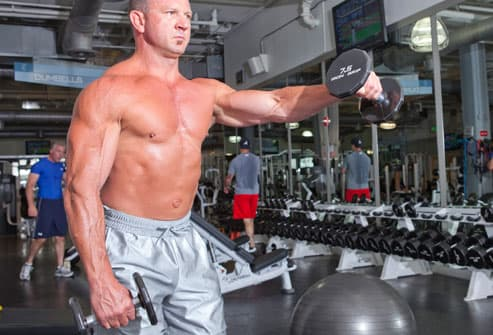 Man doing front shoulder raise with dumbbells
