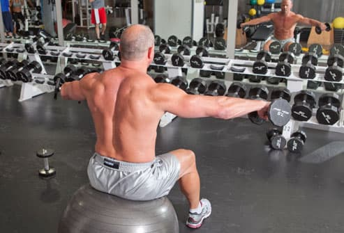 Man doing lateral shoulder raise on stability ball