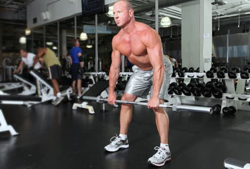 Trainer showing Romanian dead lift with barbell