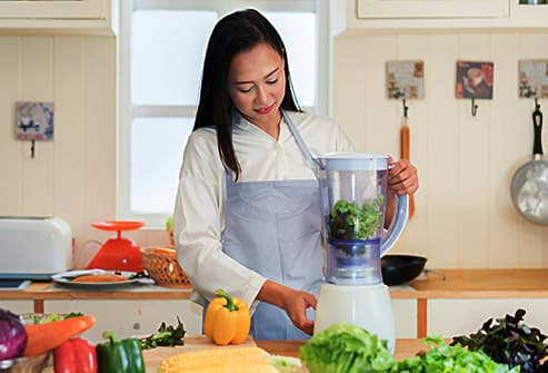 woman juicing greens