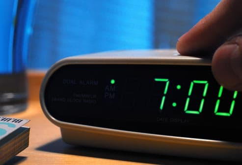 person turning off alarm clock