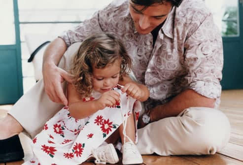 dad helping girl tie shoes