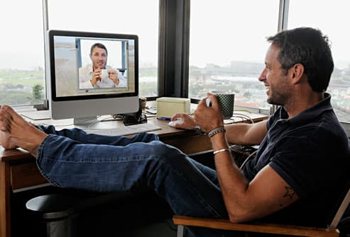 man in video conference call with therapist