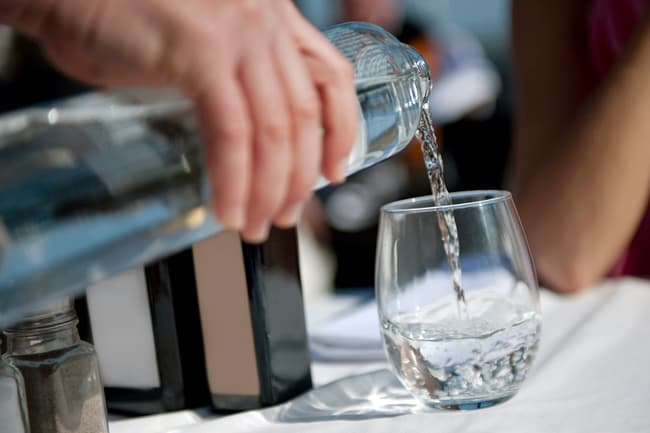 photo of waiter pouring water in restaurant