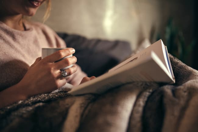 photo of woman reading book at night