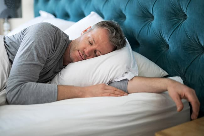 photo of man asleep in bed