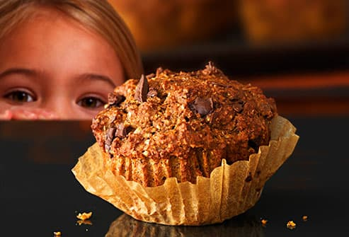 young girl spying banana bran muffin