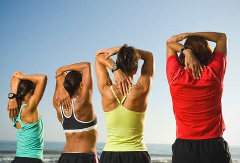 Group of Women Stretching on Beach