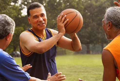 Mature man playing basketball with friends