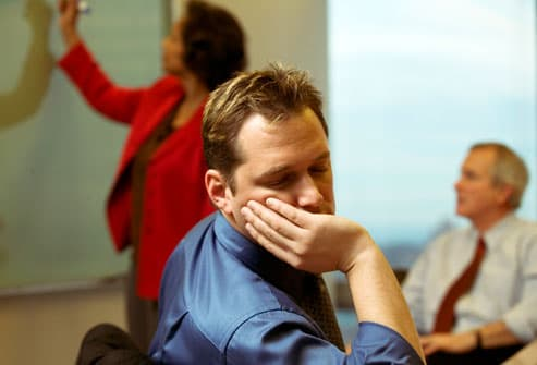 Young businessman dozing off in a meeting