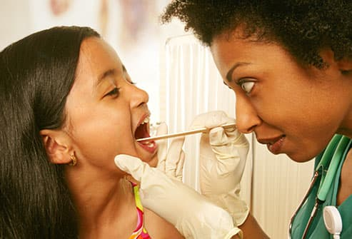 Doctor checking young girls tonsils