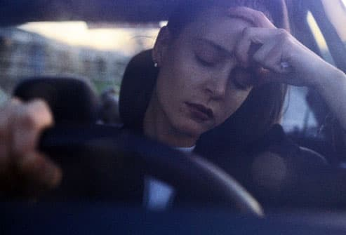 Woman dozing at the wheel of her car