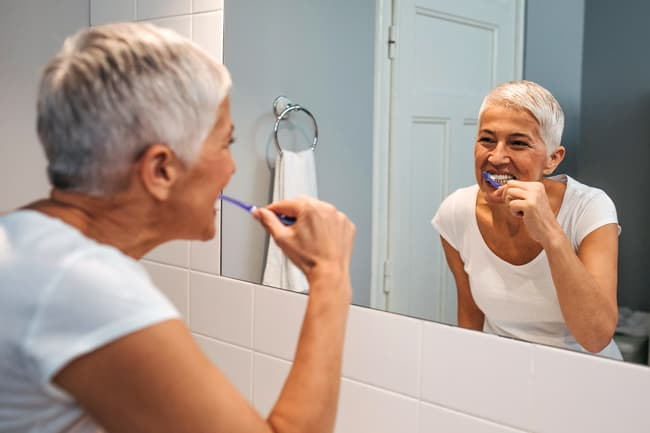photo of woman brushing her teeth
