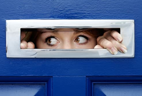 Young woman peering out of mail slot in front door