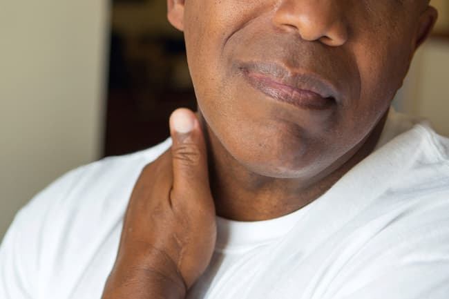 man rubbing tense neck muscles