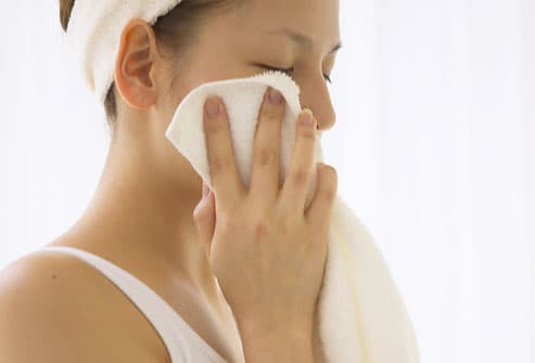 Woman washing around eye with washcloth