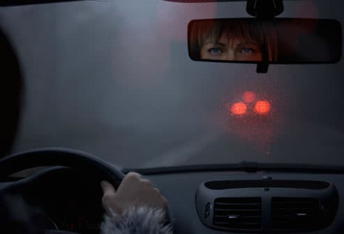 Woman looking in rear view mirror