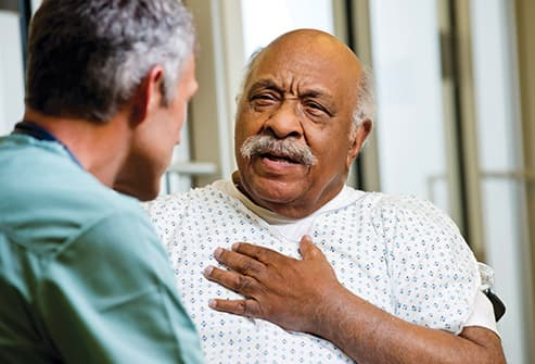 senior man describing chest pain to doctor