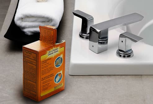 Box of baking soda next to bathtub faucet