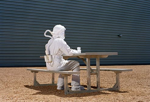 Man in hazmat suite sitting alone at table