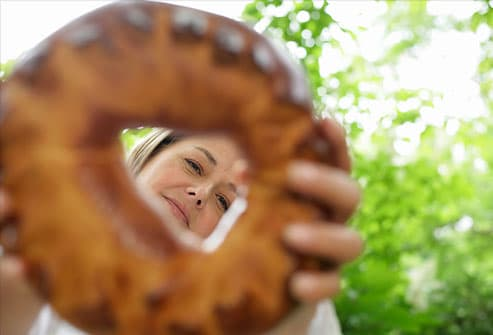 Woman looking through the center of big bagel