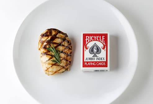 Grilled chicken and deck of cards on plate