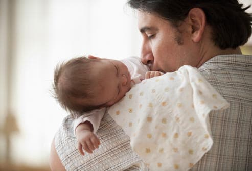 father holding sleeping infant