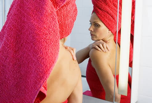Woman in towel checking skin in bathroom mirror