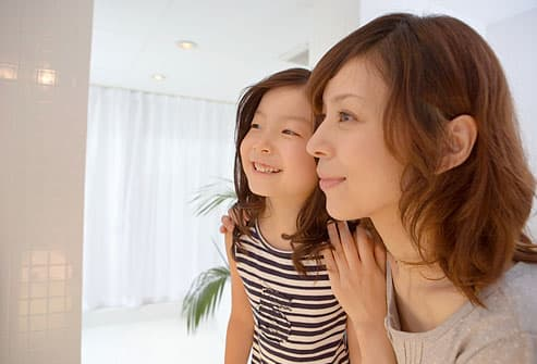 mother and daughter looking into mirror