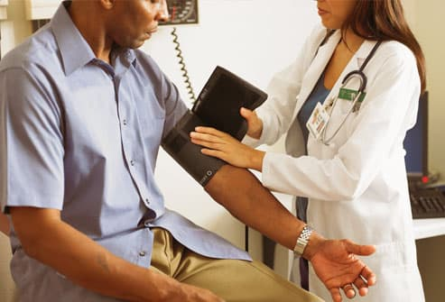 Man having blood pressure checked by doctor