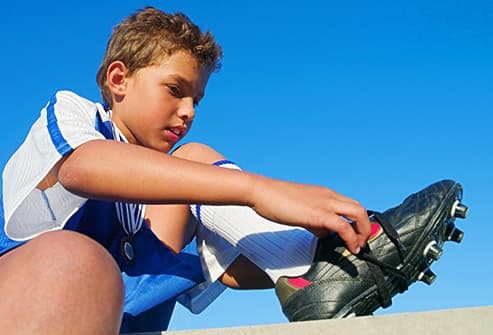 boy tying soccer cleats