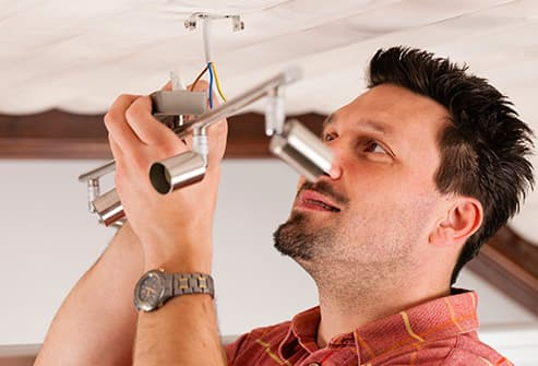 man installing ceiling light