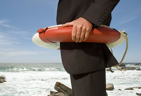 Businessman on a beach wearing a life-preserver