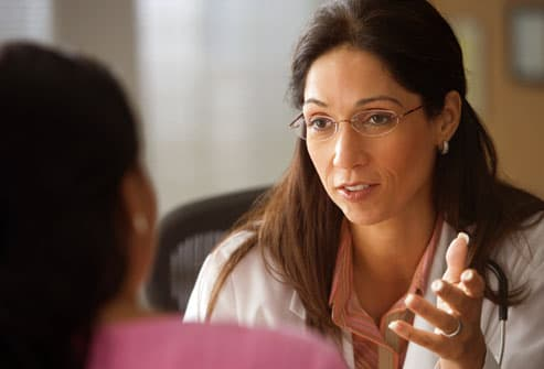 Female, Hispanic doctor talking to a woman