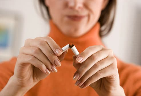 Woman snapping an unlit cigarette in half