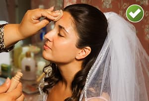 Stylist applying concealer to brides face