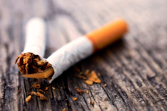 photo of broken cigarette on wooden surface