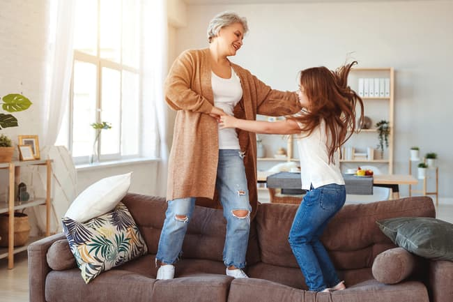 photo of mother and daughter jumping on sofa