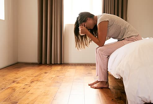 woman crying on bed