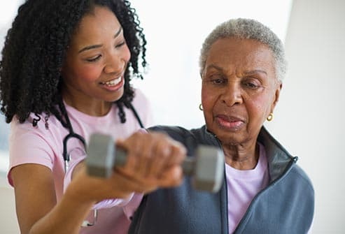 nurse helping woman exercise