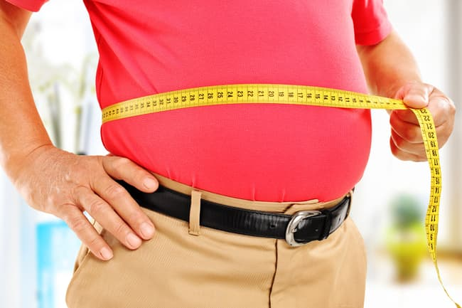 man measuring belly fat
