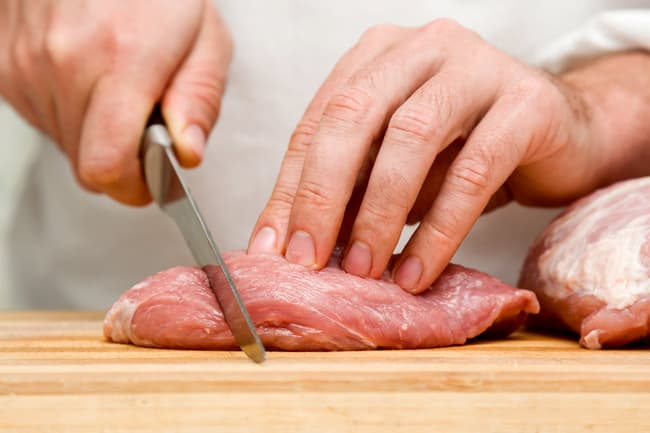 person cutting pork