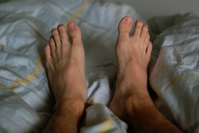 photo of feet in bed at night