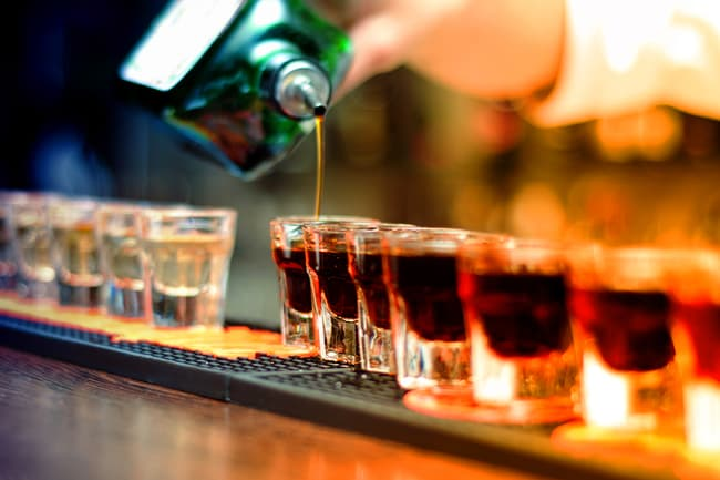 photo of shots of liquor on bar