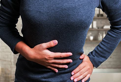 woman holds stomach