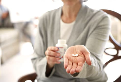 Woman holding hand out with pills in palm