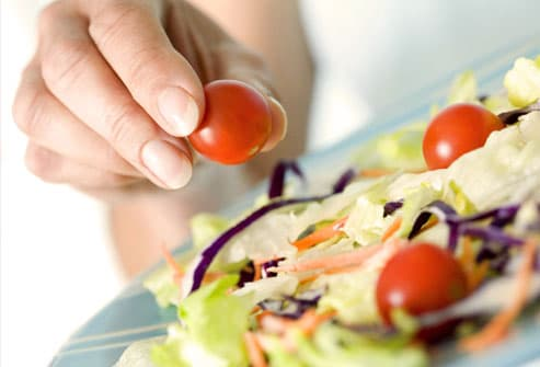 Woman picking cherry tomato off of salad