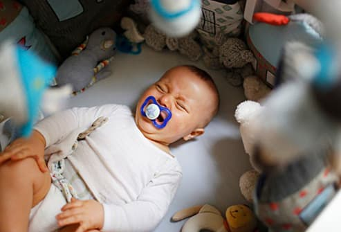 baby surrounded by stuffed toys
