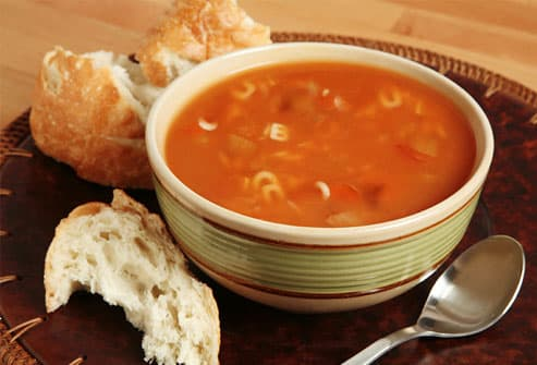 Bowl of alphabet soup with fresh bread